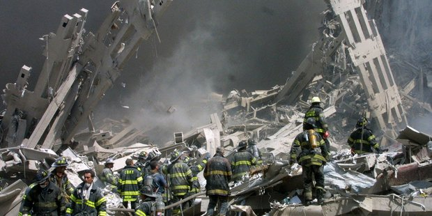 Firefighters make their way through the rubble after two airliners crashed into the World Trade Center. Photo / AP