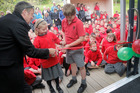 WELCOME: St John's Hill School principal Michael Fitzgerald holds the ribbon being cut by Amy Benadie and William Herd. PHOTO/BEVAN CONLEY