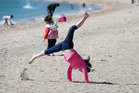 Hayley Monson, 7, makes the most of the warmer weather doing cartwheels in Misson Bay. Photo / Brett Phibbs