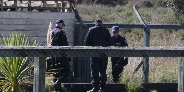 Police search near a burnt out house at Hokio Beach in March. Photo / Cherie Taylor