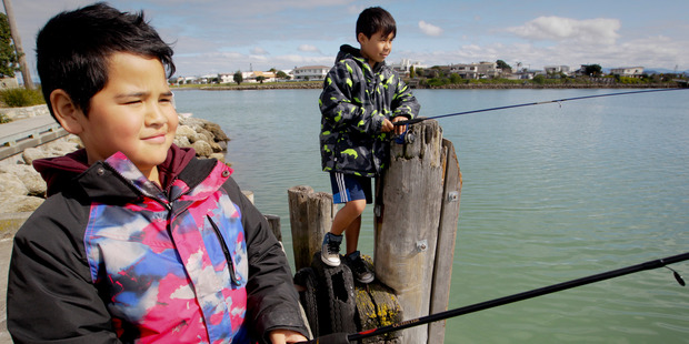 Royil Graham and Rapaira Wilson of Hastings make the most of the region's return to spring by fishing at Napier's Iron Pot in Ahuriri on Sunday. Photo / Warren Buckland