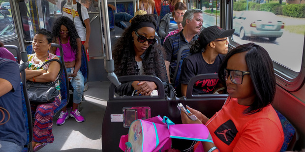 Diamond Reynolds, center, along with her sister, Ariel Doty, foreground, and other family and friends take a shuttle bus to the Minnesota State Fair. Photo / The Washington Post