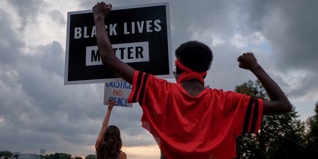 Demonstrators gather on Aug. 29 for a vigil near the spot where Philando Castile was fatally shot by a police officer. Photo / The Washington Post
