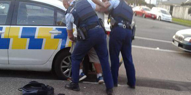 Police detaining a suspect at the time of the brawl. Photo / Supplied