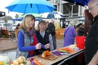 BROLLIED: Umbrellas were out at the Home and Garden Show in Napier. Pictured are Taradale women Dawn Lynn (left) and Julie Drake, with Frank Roebuck, from Kitchen Adventures. PHOTO/DUNCAN BROWN.