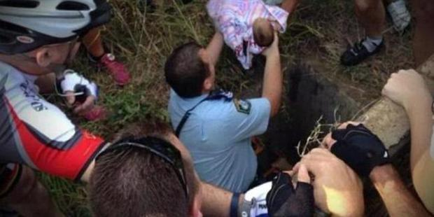 The dramatic moment the baby was rescued after five days down a 2.4m drain where he was left by his mother in November 2014. Photo / Supplied