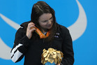Gold medalist Mary Fisher of New Zealand listens to the sound of the medal on the podium at the medal ceremony for the Women's 100m Backstroke - S11 Final. photo / Getty
