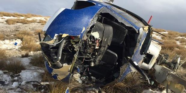 The wreckage of the helicopter that tipped over while landing on Mt Sale, on the Crown Range, on Monday. Photo / NZ Police