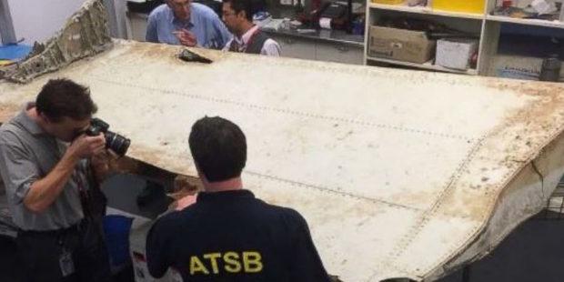 Australian Transport Safety Bureau investigators examine the wing flap from MH370. Photo / ATSB