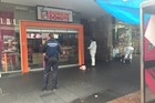 Police officers examine the scene of the death on Auckland's Queen St. Photo / Supplied