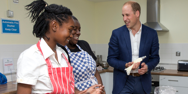 Britain's Prince William ices a cake during a baking class with young people and volunteers on a visit to Caius House Youth Centre in London. Photo / AP