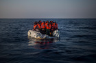 Refugees earlier this month wait aboard a partially punctured rubber boat to be assisted, during a rescue operation on the Mediterranean Sea near Libya. Photo / AP