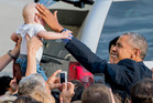 While greeting well-wishers after arriving at John F. Kennedy International Airport in New York, President Barack Obama reaches out to Desmond Hatfield-Rudin, 8 months old. Photo / AP