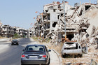 Damaged buildings and rubble line a street in Homs, Syria. Photo / AP