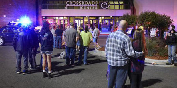 People stand near the entrance on the north side of Crossroads Center mall after a stabbing incident in the mall. Photo / AP