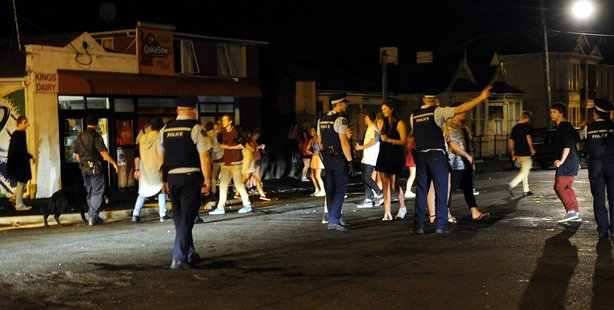 Police clear Castle Street of party goers after a large crowd gathered and lit several fires on Saturday night. Photo / ODT