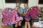 St Patrick's Catholic Primary School students Kate Wield and Izzie Gibson give away pyjamas for foster children. Photo / Christchurch Star