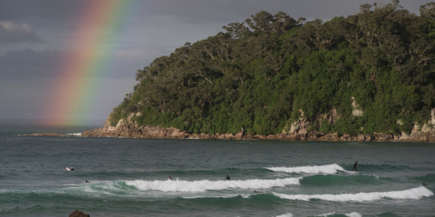 Changeable spring conditions are seen as a rainbow touches down in Shark Alley at Mt Maunganui today. Photo/Alan Gibson