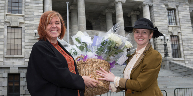 Green MP Jan Logie receives a basket of roses from Camilla Belich, of the CTU, to mark 123 years since NZ women won the right to vote. New Zealand Herald photo by Mark Mitchell.