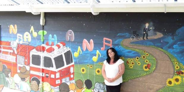 Angela Middlemiss stands in front of a mural painted in her son Nathan Booker's honour at the IHC centre in Palmerston North. High needs teen, Nathan, aged 14, drowned in a bath at Idea's Woburn Famil