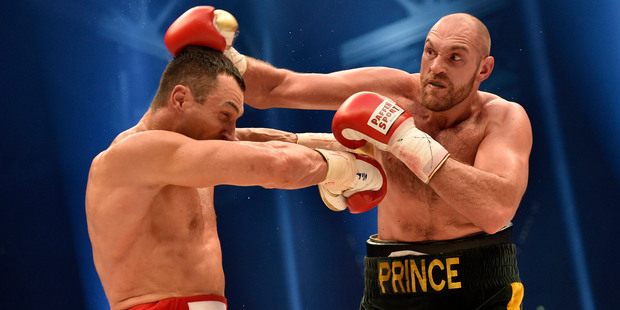 Ukraine's Wladimir Klitschko, left, and Britain's Tyson Fury compete in a world heavyweight title fight for Klitschko's WBA, IBF, WBO and IBO belts. Photo / AP