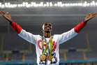 Britain's Mo Farah celebrates winning the gold medal, in the men's 5000-meter medals ceremony, during the athletics competitions. Photo / AP.