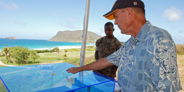 Patrick Cross, specialist at the Hawaii Natural Energy Institute at the University of Hawaii at Manoa, shows a model of the Lifesaver wave energy machine. Photo / AP
