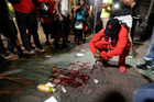 A man squats near a pool of blood after a man was injured during a protest of Tuesday's fatal police shooting of Keith Lamont Scott in Charlotte. Photo / AP