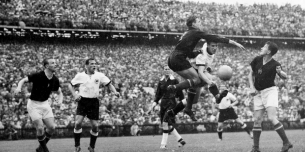 Hungarian goalkeeper Gyula Grosits, third from right, jumps to clear the ball from German right-winger Helmuth Rahn, second from right, during the Football World Cup Final. Photo / AP.