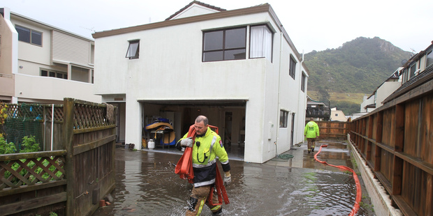 Firemen pump water out of a flooded Commons Ave property at Mount  Maunganui  in 2013. Photo/File