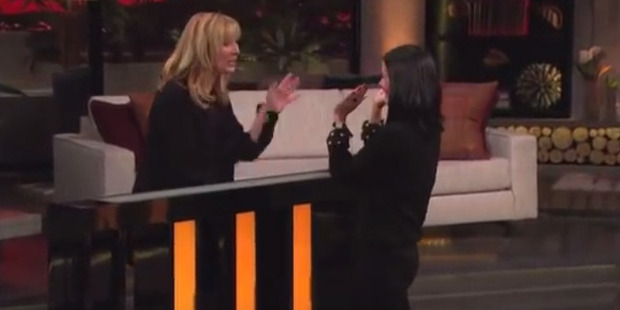 Lisa Kudrow and Courteney Cox high five after a Friends trivia game.
