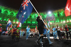 Gold and silver medallist Liam Malone carries the New Zealand flag during the closing ceremony of the Rio 2016 Paralympic Games at Maracana Stadium. photo / Getty