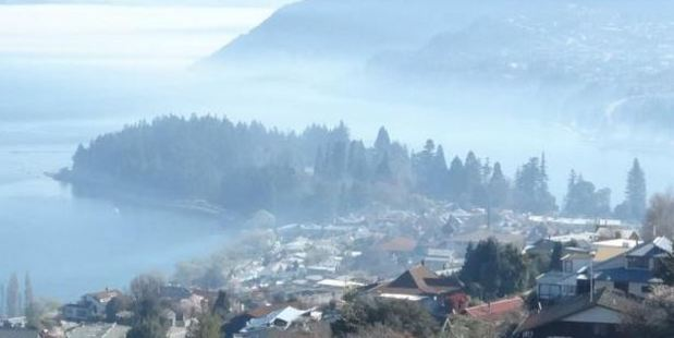 A burn-off across Lake Wakatipu smothers Queenstown in smoke yesterday. Photo / David Williams