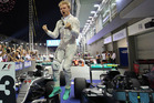 Mercedes driver Nico Rosberg of Germany jumps off his car as he celebrates after winning the Singapore Formula One Grand Prix. Photo / AP