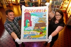 Tharron Bloomfield and Kathy Nichols hold up Boyhood Memories, one of the tea towels from Richard Hill's collection, which will feature in Every Tea Towel Tells A Story. Photo / Ben Fraser
