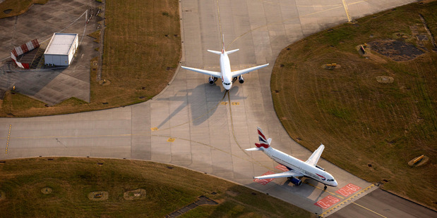 Two British Airways aircrafts, stand on the perimeter of the runway at London Heathrow Airport. Photo / Bloomberg