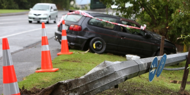 A car with a spacesaver tyre on the rear lost control and smashed into a lamp post before it stopped on a bank above a house. Photo / Michael Cunningham