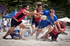 Cullun Armstrong from Tauranga Sports is scragged by the Arataki defence at last year's beach rugby at Mount Main Beach.