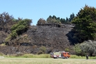 A large scrub fire at Poraiti on Friday afternoon blackened a hillside as it burnt through property boundaries but left houses unscathed. Photo / Duncan Brown
