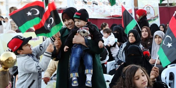Libyan woman and children wave their national flags during a demonstration against a UN-sponsored agreement on forming a national unity government. Photo / AP