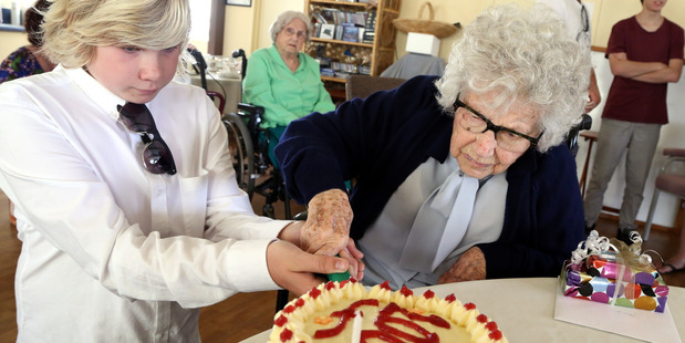 A HUNDRED OF THE BEST: Centenarian Trixie Seccombe cuts her birthday cake with help from her 13-year-old grand-nephew, Henry Coyle. PHOTO/STUART MUNRO