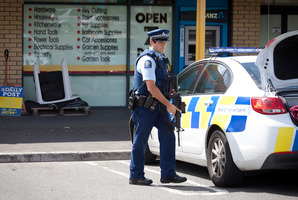 Police outside the Hammer Hardware and Lotto in the Te Ngae Shopping Centre. Photograph by Andrew Warner.
