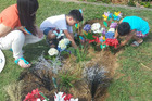 Nadene Lomu and her two sons place flowers on Jonah Lomu's grave at Manukau Memorial Gardens.