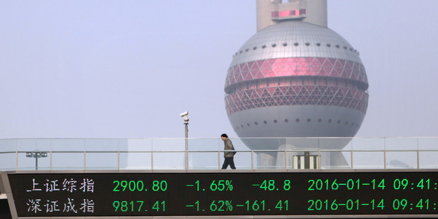 A pedestrian walks across an elevated bridge showing index figures for the Shanghai stock exchange. Photo / AP