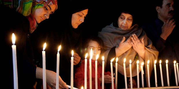 Pakistani women light candles during a vigil for victims of the Bacha Khan University attack. Photo / AP