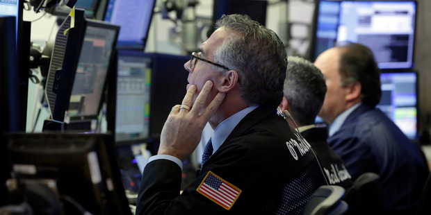 Trader Kenneth Polcari, left, works with colleagues in their booth on the floor of the New York Stock Exchange. Photo / AP