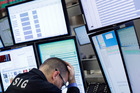 A trader rests his head in his hand at the New York Stock Exchange. Photo / AP