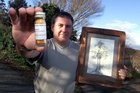 Doug Mende with a phial of totarol, and a pencil drawing of New Zealand's oldest-standing totara. File Photo / Lynda Feringa.