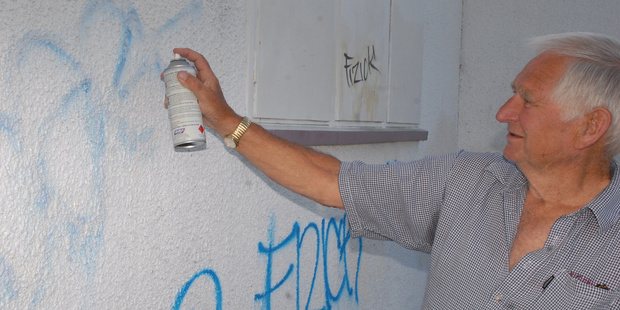 Wyvern Laing, president of the Wairarapa Senior Citizens and Beneficiaries Association, clears graffiti from the building in Perry St, Masterton. PHOTO/GERALD FORD