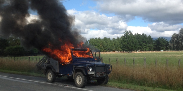 Flames destroy the cab of a Landrover after the driver parked at the roadside on Ngaumutawa Rd in Masterton yesterday morning to escape the blaze. PHOTO/BRIAN ARMSTRONG